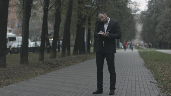 Thumbnail for Bearded Businessman In Park Alley Talking By Phone