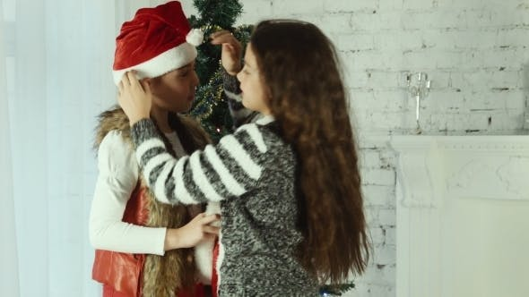 Thumbnail for Two Girls Wear Santa Hats To One Another