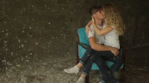 Boy And Girl Kissing On Chair
