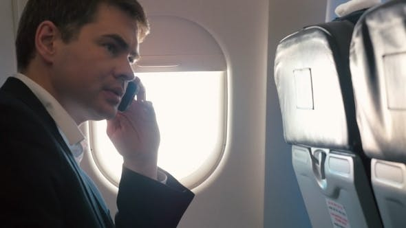 Thumbnail for Young Man Having a Business Phone Talk In Plane