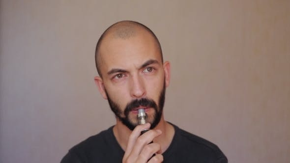 Thumbnail for Guy With a Beard Smokes Electronic Cigarette
