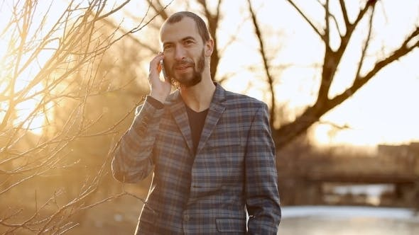 Thumbnail for Guy With Beard Speaks On The Phone Outdoor