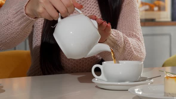 Woman Pouring Aromatic Tea Into Her Cup at the Coffee Shop
