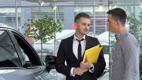 Thumbnail for Friendly Car Dealer Helping His Male Customer Choosing Automobile To Buy