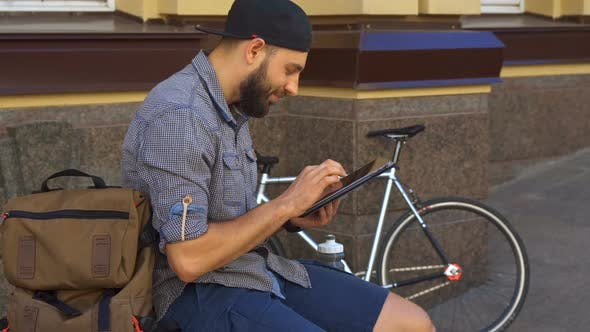 Thumbnail for Cyclist Uses Tablet on the Street