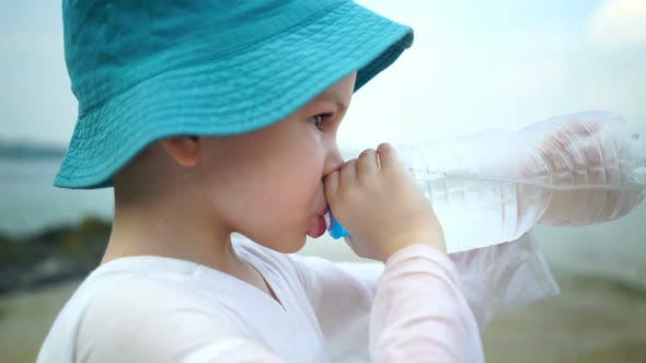 Thumbnail for Boy Drinks Clear Water From a Plastic Bottle on a Sunny Day