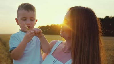 Mother and Son in Wheat Field at Sunset