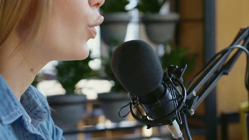 Young Woman Communicating in Modern Microphone with People