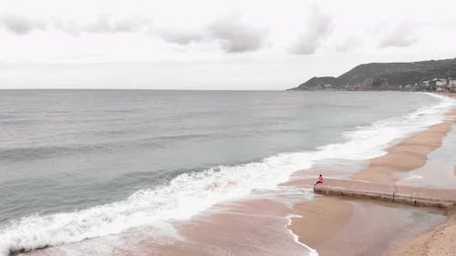 Lonely young woman sitting alone on concrete pier, looking at stormy sea with waves