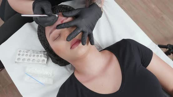 Blonde Cosmetologist Using Her Tools During a Procedure in Her Beaty Cabinet