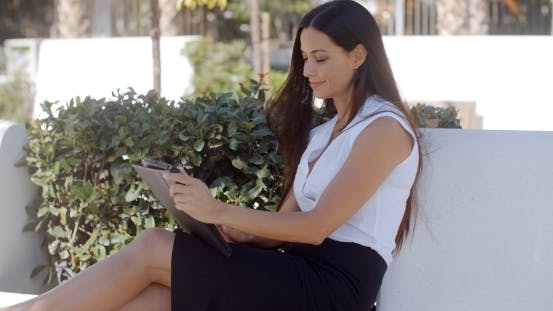 Thumbnail for Smiling Young Woman Using Her Tablet Outdoors