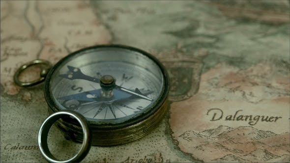 Thumbnail for A Small Compass and a Ring on Top of a Map
