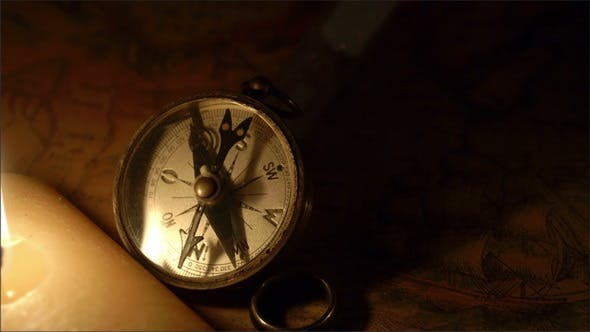 Thumbnail for A Lighted Candle Beside a Compass