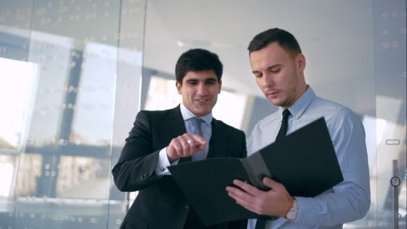 Cover Image for Two Handsome Businessman Discussing Document