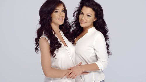 zwei attraktive freundinnen posieren arm in arm