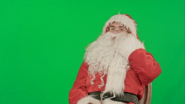 Thumbnail for Santa Claus Calling With a Mobile Phone On a Green