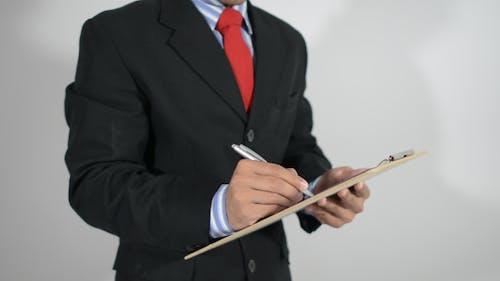 Stehender Geschäftsmann Schreiben auf Zwischenablage