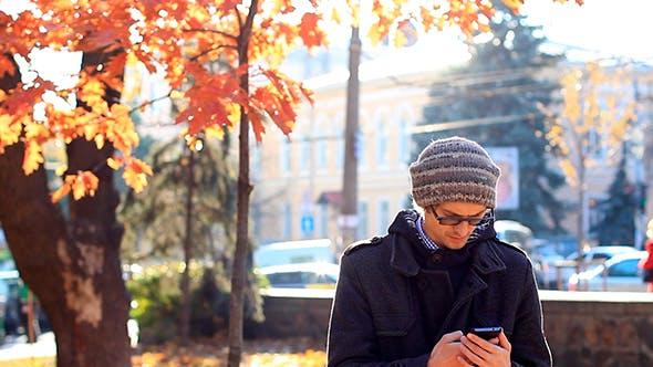 Thumbnail for Junger Mann mit einem Telefon in der Park