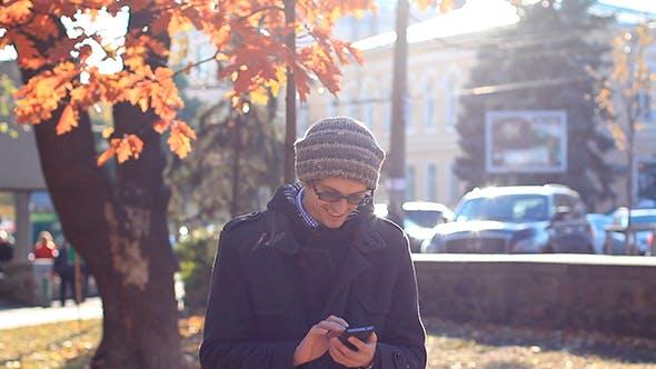 Cover Image for Junger Mann mit einem Telefon in der Park