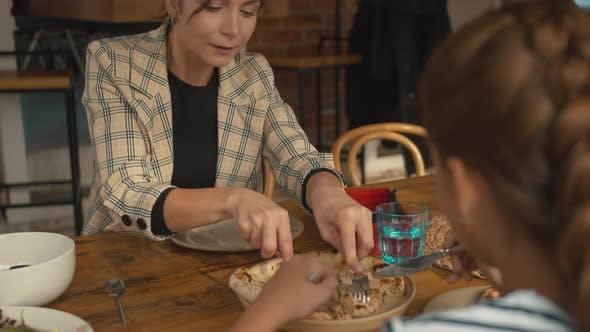 Frau nimmt ein Stück Pizza und setzt auf Teller