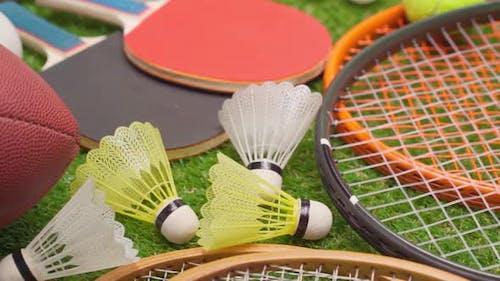 Verschiedene Sportgeräte auf Gras einschließlich Schläger Bälle Federbälle und Ball Close Up