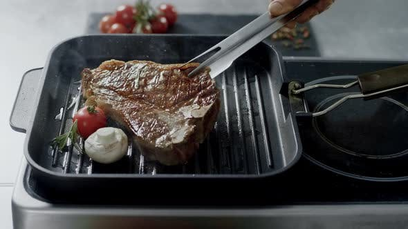 Thumbnail for Chef Cooking Steak at Griddle Pan. Closeup Man Hands Turning Steak with Tongs.