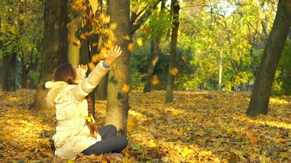 Thumbnail for Young Girl Having Fun Throwing Yellow Leaves.
