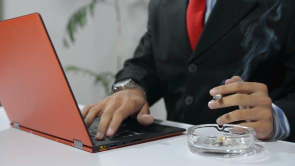 Thumbnail for Man Smoking and Working on Laptop