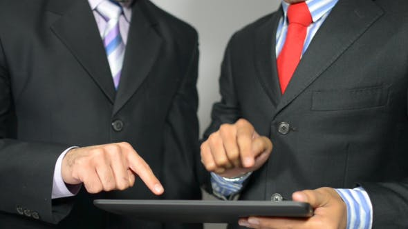 Cover Image for Businessmen Discussing Financial Info on Tablet PC