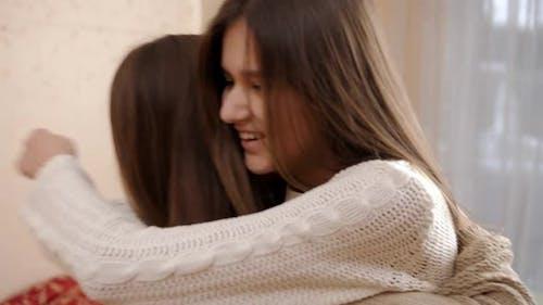 Zwei glückliche Mädchen, die nach dem Umarmen lächeln und umarmen