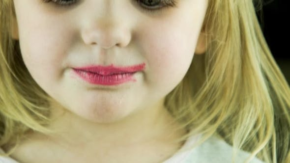 Thumbnail for The Little Cute Girl Makes Up Lips With Red