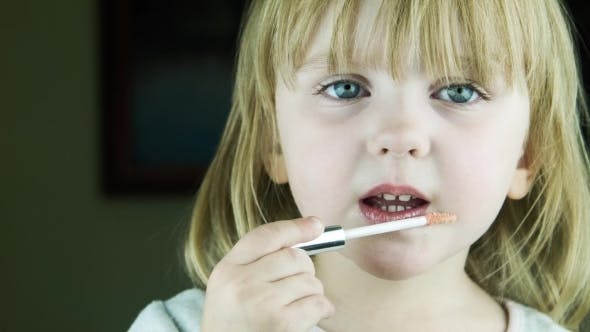Cover Image for The Little Cute Girl Makes Up To Herself Lips