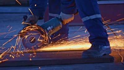 Worker Cutting The Metal