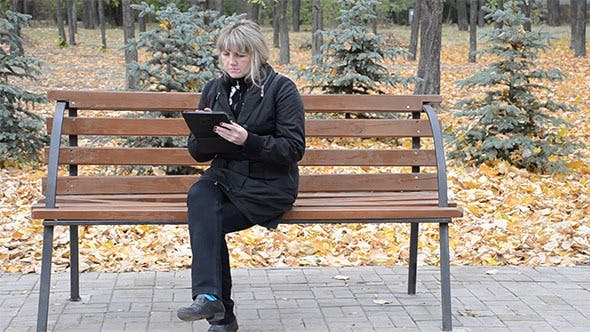 A Woman on a Bench With the Tablet