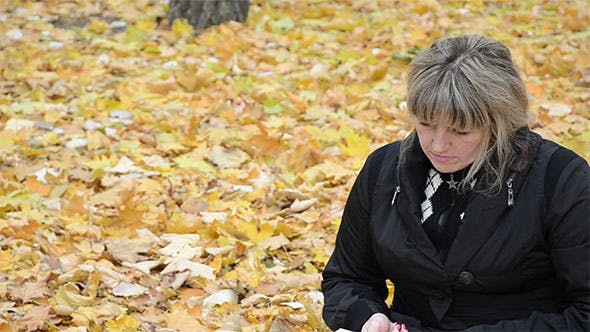 Thumbnail for Woman Sitting on Yellow Leaves Reading a Book