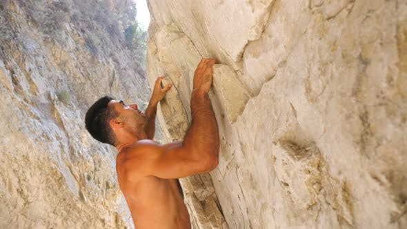 Thumbnail for Young Muscular Man Carefully Climbing at Rock. Strong Guy Ascending on Rock Peak Making Great