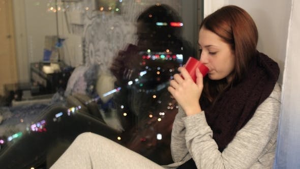 Thumbnail for Girl Sits On Window Sill And Drinks Hot Tea In Cup