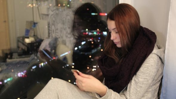Thumbnail for Girl Sits On Window Sill And Using Smartphone