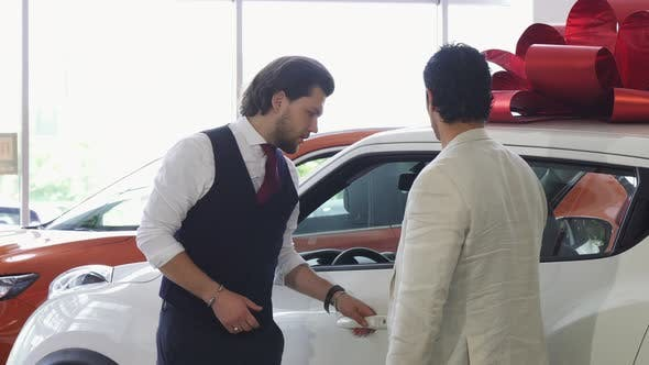 Thumbnail for Professional Car Salesman Opening Door of a Car for His Male Customer