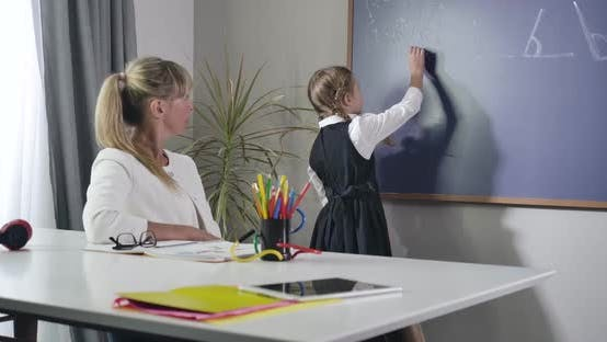 Diligent Caucasian Schoolgirl Turning To Blackboard and Writing with Chalk