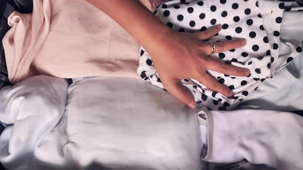 Close Up of a Woman's Hand Placing Folded Clothes Into the Luggage and Closing It