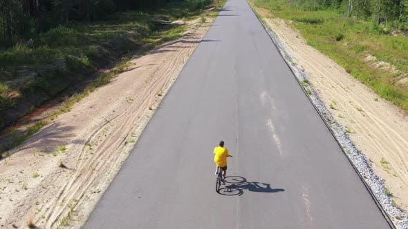 Thumbnail for Aerial View From Drone on Man Riding on Asphalt Road