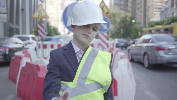 Thumbnail for Tired Little Boy in Constructor Helmet on His Head, and Uniform Looking in Camera Showing Thumb Up