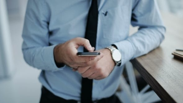 Thumbnail for Businessman Using Phone In Modern Cafe