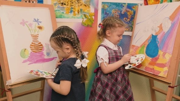 Thumbnail for Two Little Girls Standing At The Easel And Paint