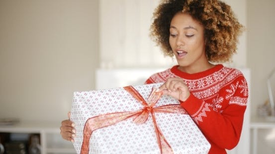 Thumbnail for Pretty Young Woman Opening Christmas Gift