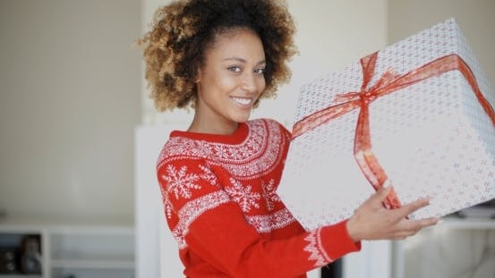 Cover Image for Happy Smiling Girl With Afro Haircut Holding Gift