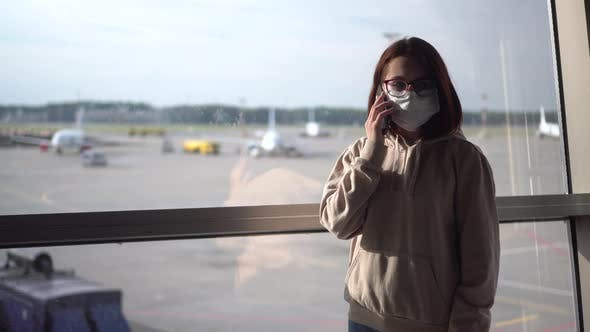 Thumbnail for A Young Woman in a Medical Mask Talks on the Phone Against the Background of a Window at the Airport
