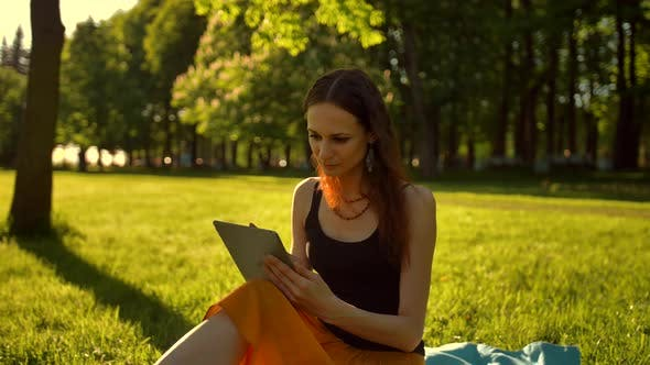 Cover Image for Young Lady Brows Her Tablet on Green Grass.