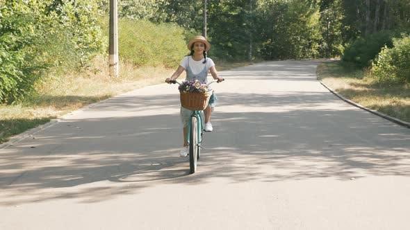 Thumbnail for Smiling beautiful girl on retro bike in sunny park.